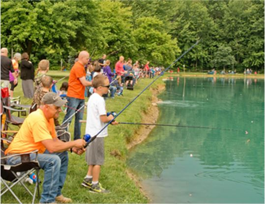 Lots of adults and children fishing in a pond