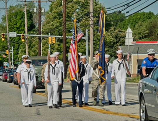 Navy officers and crew men martching with the US flag down the street