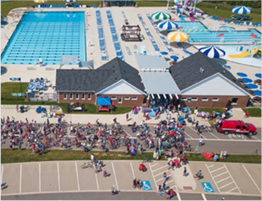 Aerial view of the pool and lots of people on bikes in front